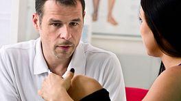 Chiropractor examining patient's knee.