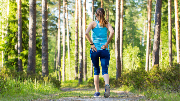 Image of woman in the woods walking with back pain
