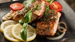 Plate of salmon with tomatoes and lemon slices