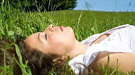Woman lying down and resting in the grass