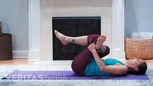 图为女性躺在垫子上做梨状肌伸展术以缓解腰部疼痛
