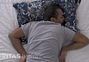 Image of a man sleeping on his stomach in an awkward position