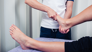 Image of physical therapist holding a patient's foot