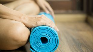 Hands resting on a rolled-up blue yoga mat