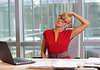 Image of woman performing a neck exercise at her desk