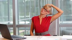 Woman stretching her neck while sitting at her desk.
