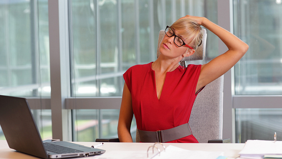woman stretching neck at desk