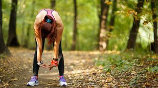 Exhausted runner stopped on a running trail.