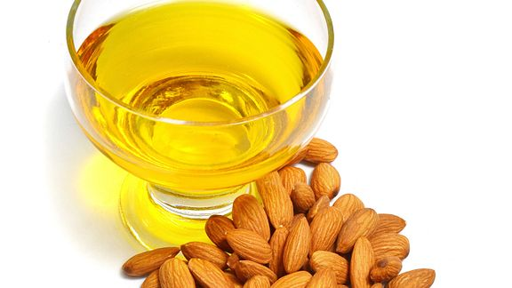 Bowl of almond oil surrounded in front of a bunch of almonds
