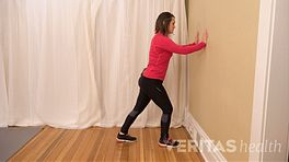 Woman doing a Standing Calf Muscle Stretch against a wall.