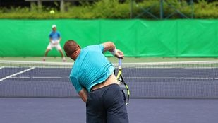 Two men playing tennis across the court from each other.