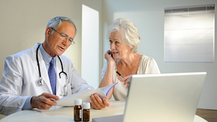 Image of doctor reviewing results at a table with a senior, female patient