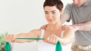 Woman working with physical therapist stretching a resistance band with both hands outstretched