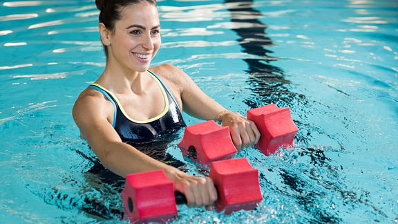 Young woman using weights in the pool