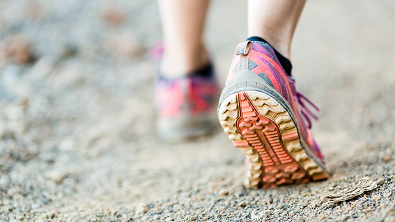 closeup image of feet walking on trail with sneakers