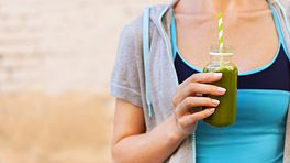 Woman drinking a green smoothie.