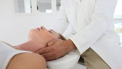 Chiropractor adjusting a supine patient's cervical spine.