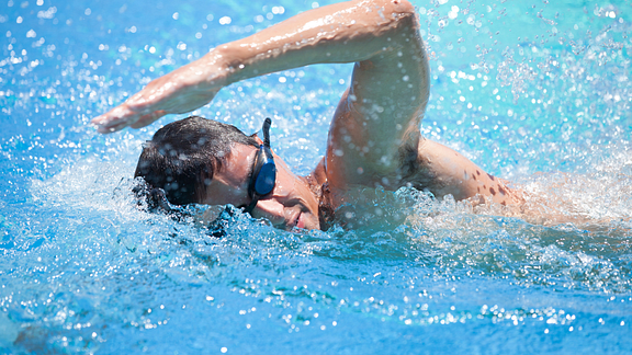 Image of a man with goggles swimming laps in a pool