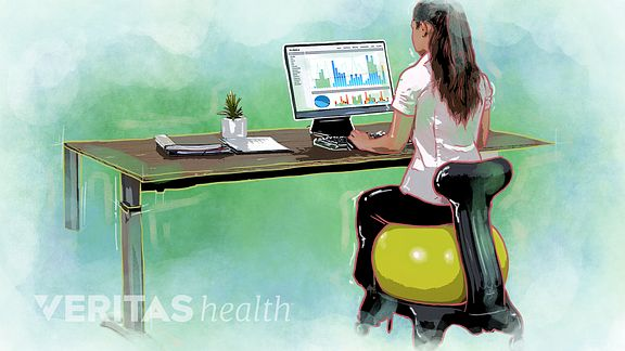 Woman using an exercise ball with a base at a desk