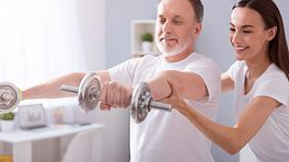 Therapist assisting patient with shoulder exercises using dumbbells.