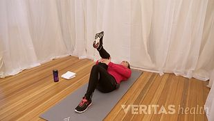 Instructor laying on her back performing the single knee to chest SI joint stretch