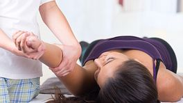 Patient lying supine on a massage table while practitioner works on the shoulder..