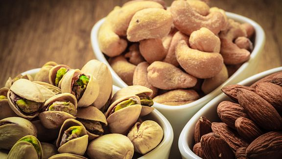 pistachios, almonds, and cashews in bowls