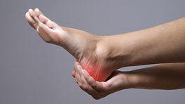 Hand cradling heel with pain