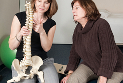 Physical therapist explaining the upper spine to a patient