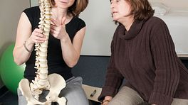 Physical Therapist educating patient using spine model