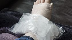 Bag of ice on wrapped foot wrapped with bandage