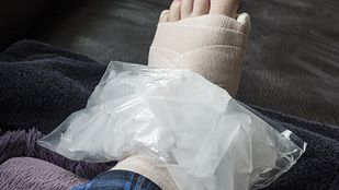 Ankle wrapped in bandage with ice on the joint.