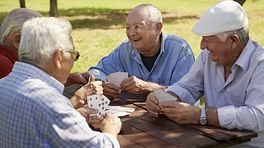 Four elderly men playing cards at a picnic table in the park