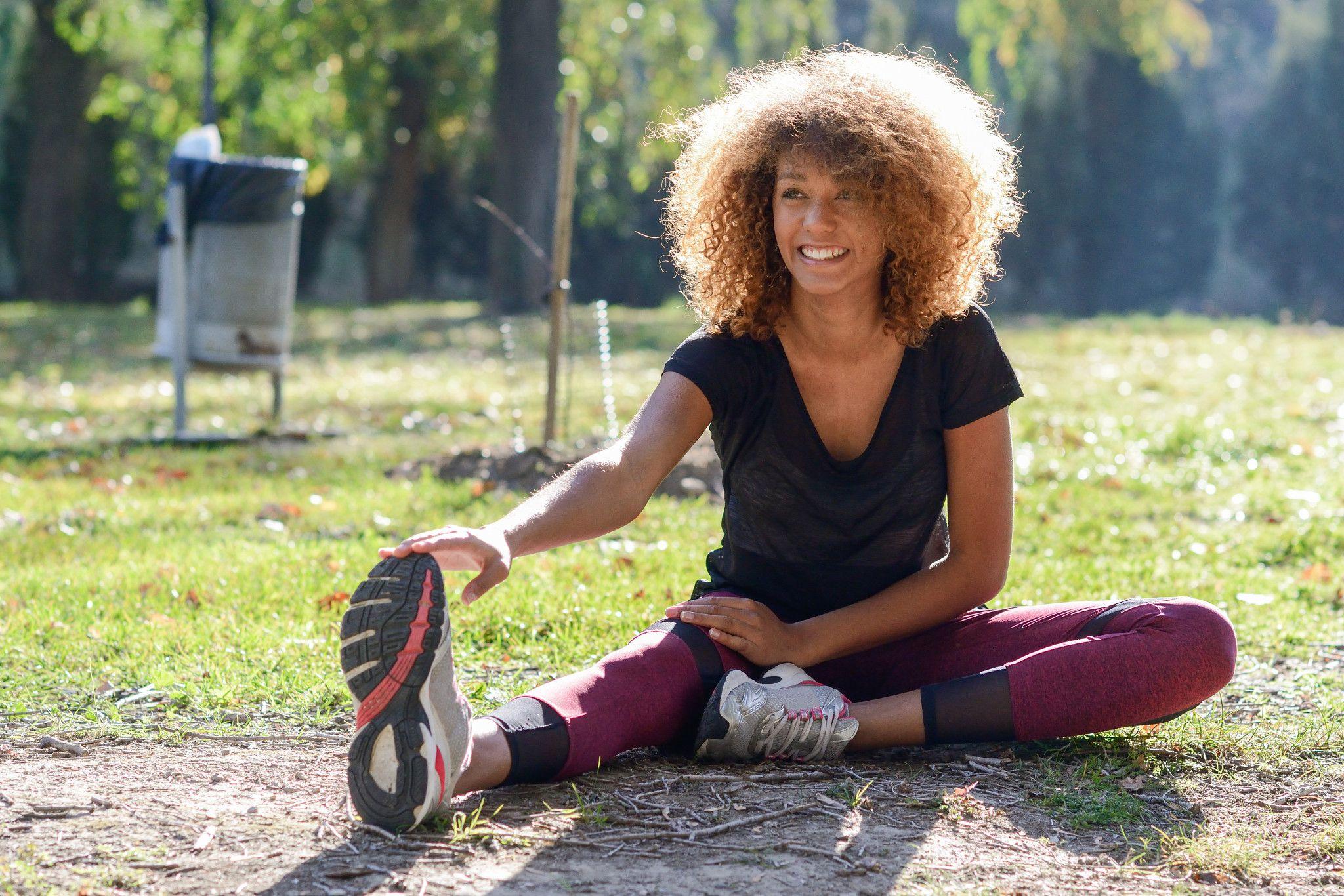 Woman doing a forward fold at the park