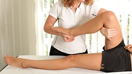 Physical therapist manipulating a patient's leg/thigh