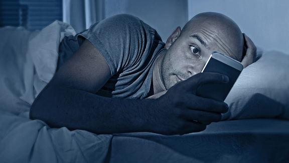 Image of a man checking his cellphone in bed