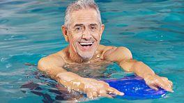 Man in a pool performing water aerobics.