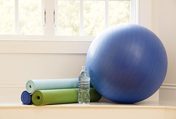 Image of exercise ball, 3 rolled up yoga mats, and a bottle of water on the floor.