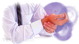 Person holding their wrist in pain