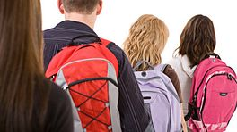 Four teenagers carrying backpacks