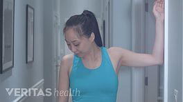 Woman doing levator scapula stretch