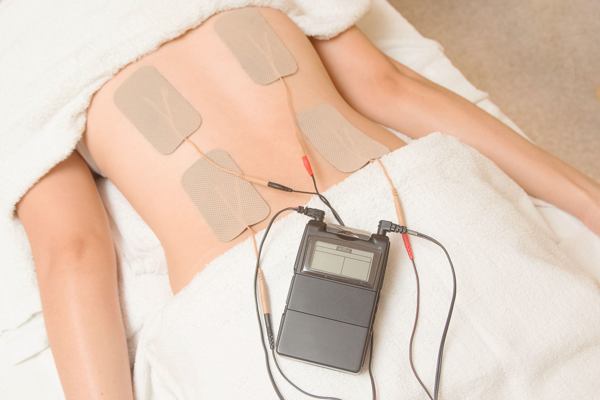 Tens unit being applied to the lower back.