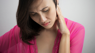 Image of a woman holding the side of her head and neck in pain