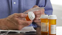 Older man reading the instructions on his prescription medications