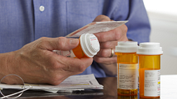 Image of and older man reading the instructions on his prescription medications