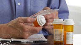 Person reading the label on a prescription pill bottle