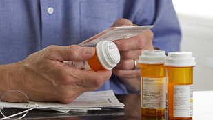 Image of person reading the label on a prescription pill bottle
