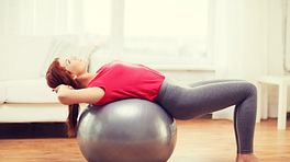 Woman performing a bridge stretch over an exercise ball.