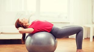 Woman doing a back bend over a large exercise ball