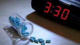 Sleeping pills spilled out next to an alarm clock